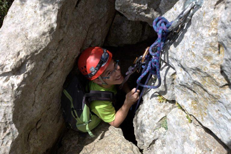 Jeune homme à la sortie d'un passage étroit du parcours aventure du Pic Saint Loup