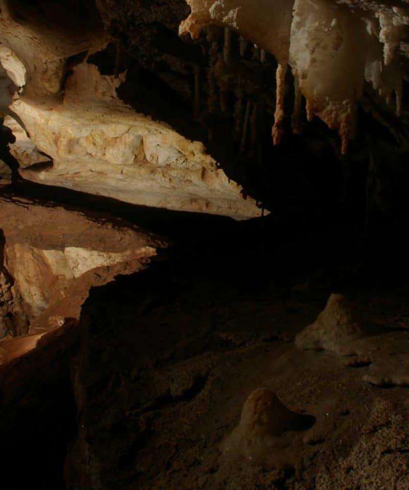 Un homme dans une des cavités de la grotte de genevaux