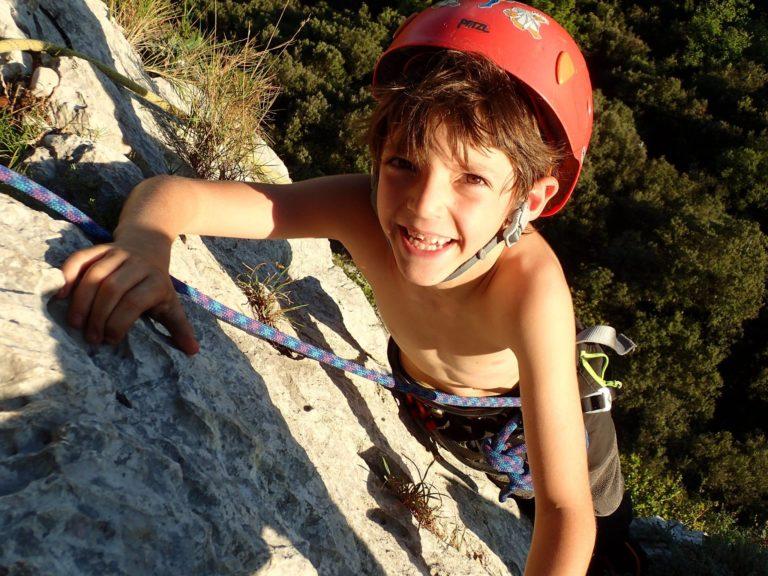 Un garçon souriant qui escalade les falaises du Thaurac
